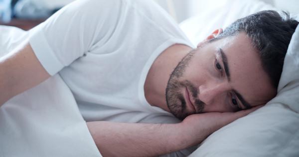 Przygnębiony mężczyzna leży w łóżku
