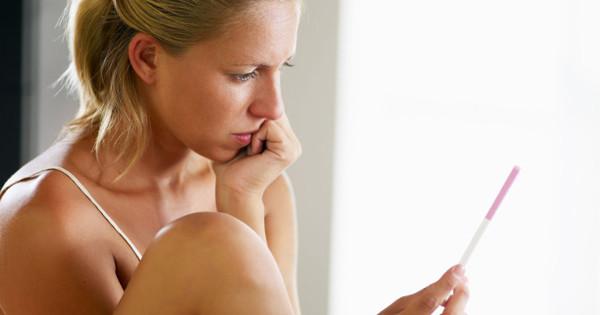 Smutna kobieta z testem ciążowym
